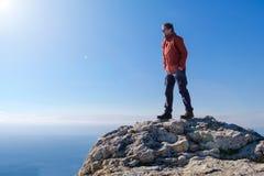 Uomo sorridente in occhiali da sole che stanno al picco della montagna della roccia Immagine Stock
