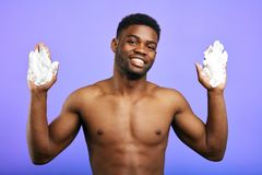 Uomo sorridente positivo che mostra le sue mani in crema fotografia stock libera da diritti