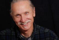 Uomo sorridente su priorità bassa nera Immagini Stock Libere da Diritti