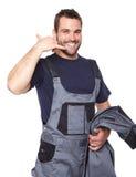 Uomo sorridente in vestiti da lavoro che mi rendono ad una chiamata segno Fotografia Stock