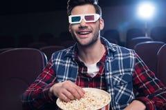 uomo sorridente in vetri 3d con il film di sorveglianza del popcorn Immagini Stock