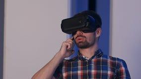 Uomo sorridente in vetri di realtà virtuale che hanno conversazione sul telefono Immagini Stock
