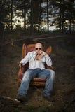 Uomo sottile in una sedia d'annata Fotografie Stock Libere da Diritti