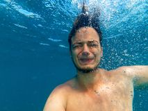 Uomo sotto acqua, annegante con un'espressione di timore e dell'orrore sul suo fronte Immagine Stock