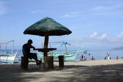 Uomo sotto il parasole sulla spiaggia di sabbia bianca siluette Fotografia Stock