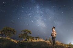 Uomo sotto le stelle della galassia della Via Lattea immagini stock