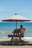 Uomo sotto un ombrello di spiaggia Fotografie Stock