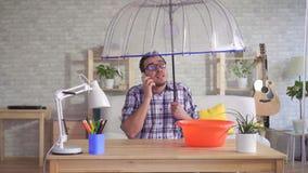 Uomo sotto un ombrello sui rapporti del telefono circa l'inondazione in suo appartamento stock footage