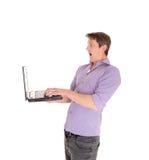 Uomo spaventato al suo computer portatile Immagini Stock