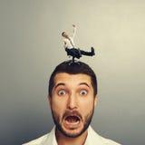 Uomo spaventato con il piccolo uomo pazzo sulla testa Immagini Stock