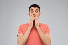 Uomo spaventato in maglietta di polo sopra fondo grigio Fotografie Stock