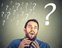 Uomo spaventato sembrante divertente sorpreso di affari con molti punti interrogativi Fotografie Stock