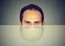Uomo spaventato sospettoso che dà una occhiata da sotto nascondersi della tavola Immagini Stock