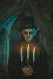 Uomo spaventoso con le candele nei candelabri Immagini Stock Libere da Diritti