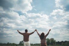 Uomo spensierato e donna che sollevano le mani fino al cielo Fotografie Stock Libere da Diritti