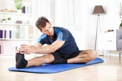Uomo splendido che esegue allungamento del tendine del ginocchio a casa Fotografie Stock Libere da Diritti