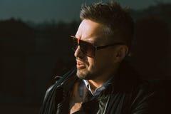 Uomo splendido in occhiali da sole che guardano da parte vicino alla parete nera Fotografia Stock Libera da Diritti