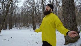 Uomo sportivo barbuto che salta con il salto della corda nella foresta di inverno stock footage
