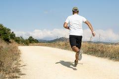 Uomo sportivo che corre giù la pista sabbiosa. fotografia stock