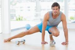 Uomo sportivo che fa allungando esercizio nello studio di forma fisica Fotografie Stock