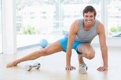Uomo sportivo che fa allungando esercizio nello studio di forma fisica Immagine Stock