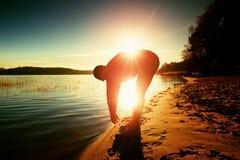 Uomo sportivo che fa mattina che pareggia sulla spiaggia del mare alle siluette luminose di alba Fotografie Stock