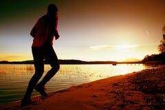 Uomo sportivo che fa mattina che pareggia sulla spiaggia del mare alle siluette luminose di alba Fotografie Stock Libere da Diritti