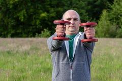 Uomo sportivo che giudica le teste di legno rosse con le armi stese nella parte anteriore Fotografia Stock