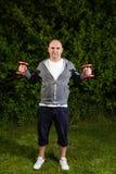 Uomo sportivo che tiene due teste di legno rosse nell'aria Fotografia Stock Libera da Diritti