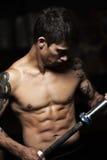 Uomo sportivo giovane con il bilanciere nudo della tenuta del torso Fotografia Stock