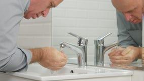 Uomo stanco in bagno che lava il suo fronte con acqua dolce dal rubinetto del lavandino fotografia stock