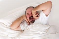 Uomo stanco che allunga in uno sforzo per svegliare immagine stock libera da diritti