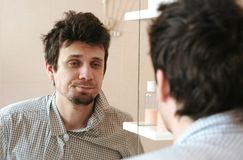 Uomo stanco che appena ha svegliato gli sguardi alla sua riflessione nello specchio e vede il suo aspetto trasandato Raddrizza il Immagine Stock