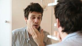 Uomo stanco che appena ha svegliato gli sguardi alla sua riflessione nello specchio e vede il suo aspetto trasandato Raddrizza il stock footage