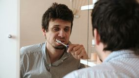 Uomo stanco che appena ha svegliato la spazzola i suoi denti, esamina la sua riflessione nello specchio e vede il suo aspetto tra video d archivio