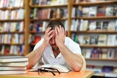 Uomo stanco che dorme nella biblioteca Immagine Stock