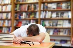 Uomo stanco che dorme nella biblioteca Immagini Stock Libere da Diritti