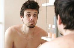 Uomo stanco che ha svegliato appena gli sguardi alla sua riflessione nello specchio e sorpresa Fotografia Stock