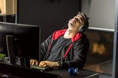 Uomo stanco che lavora dal computer in appartamento Immagini Stock