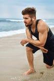 Uomo stanco che riposa dopo avere corso sulla spiaggia Allenamento di sport all'aperto Immagine Stock Libera da Diritti