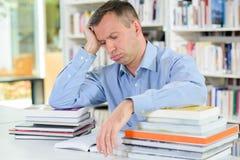 Uomo stanco con i libri della pila Fotografia Stock Libera da Diritti