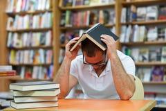 Uomo stanco nella biblioteca Fotografia Stock Libera da Diritti