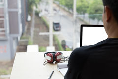uomo startup che usando su un computer portatile mentre sedendosi la tavola di legno MA Fotografie Stock