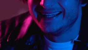 Uomo strano che ride in night-club dopo il fumo delle droghe, effetto della marijuana, primo piano video d archivio