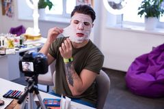 Uomo straordinario risoluto con i tatuaggi che scoprono maschera bagnata immagini stock