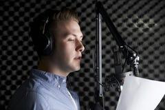 Uomo in studio di registrazione che convince microfono Immagine Stock