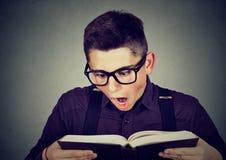 Uomo stupito che legge un libro Immagini Stock Libere da Diritti