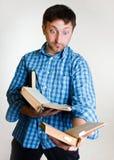 Uomo stupito con i libri a disposizione Immagine Stock