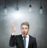 Uomo stupito con spese generali delle lampadine e della bocca aperta fotografie stock