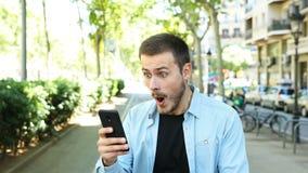 Uomo stupito facendo uso degli sguardi del telefono alla macchina fotografica archivi video